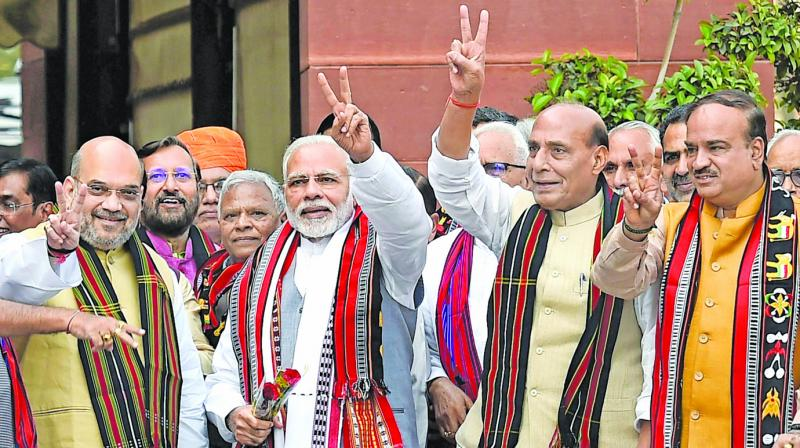 Prime Minister Narendra Modi waves the victory sign along with BJP president Amit Shah and Union ministers Rajnath Singh and others at Parliament on the first day of the second phase of the Budget Session in New Delhi. (Photo: PTI)