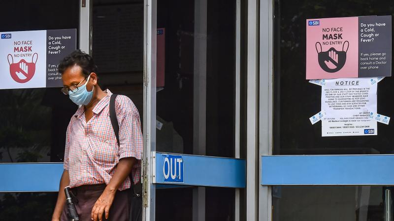 A man wearing a mask leaves a SBI office in Kolkata on Tuesday. (PTI)