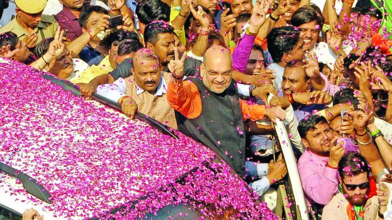 BJP president Amit Shah waves to supporters upon his arrival at the party headquarters to celebrate the party's victory in New Delhi. (Photo: Pritam Bandyopadhyay)