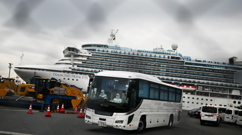 A bus with a driver wearing protective gear departs from the dockside next to the Diamond Princess cruise ship, which has around 3,600 people quarantined onboard due to fears of the new COVID-19 coronavirus, at the Daikoku Pier Cruise Terminal in Yokohama port on February 14, 2020. Japanese authorities were preparing February 14 to move some older passengers who tested negative for the new coronavirus off the quarantined cruise ship and into government-designated lodging. (AFP)