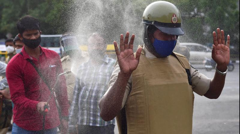 A police officer being sanitized in city market area in Bengaluru, Karnataka. PTI photo