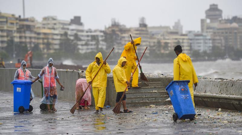Municipal workers clean garabage washed ashore by waves crashing Marine Drive promenade, during high tide, in Mumbai. PTI photo