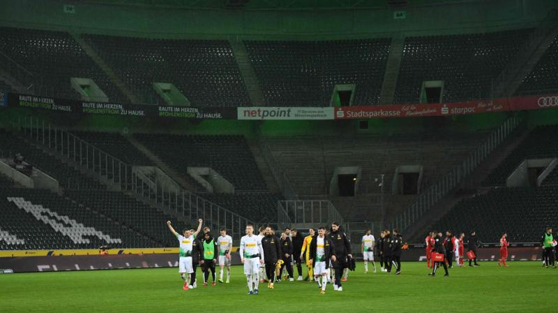 Moenchengladbach's players celebrate after the German first division Bundesliga match against Cologne on March 11. It was the first game in Bundesliga history to be played without fans. AFP Photo