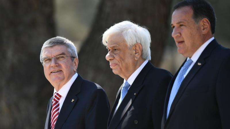 International Olympic Committee (IOC) president Thomas Bach (L) at the Olympic flame lighting ceremony in ancient Olympia on March 12, along with Greek President Prokopis Pavlopoulos (C). AFP Photo