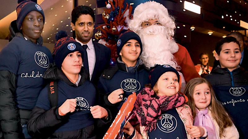 ONE OF THE FORTUNATE CLUBS? Paris Saint-Germain's Qatari president Nasser Al-Khelaïfi (Back C) and Paris Saint-Germain's French forward Kylian MBappe dressed as Santa Claus give gifts to children from the foundation of Paris Saint-Germain before last Christmas. AFP Photo
