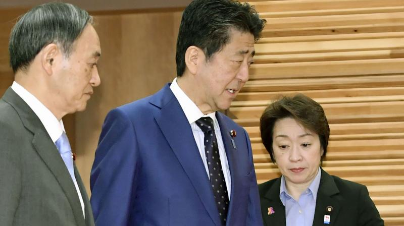 Japanese Prime Minister Shinzo Abe (C) with Olympic Minister Seiko Hashimoto (L) at a recent cabinet meeting. AP Photo