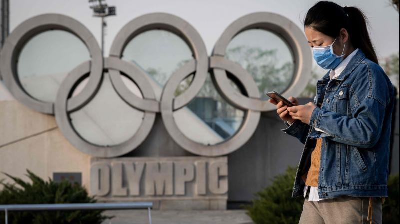 A woman wearing a face mask, amid concerns of the COVID-19 coronavirus, walks past an Olympic rings sculpture. AFP Photo