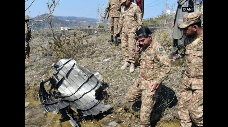 Wreckage of the F-16 Pakistan Air Force jet, which was shot down by the Indian Air Force on Wednesday, was seen being inspected by Pakistan military officers in PoK, sources said. (Photo: ANI)
