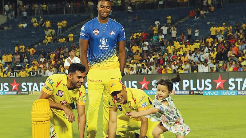 M.S. Dhoni plays with his daughter Ziva as CSK team mates Deepak Chahar (left) and Lungi Ngidi look on. (Photo:  BCCI)