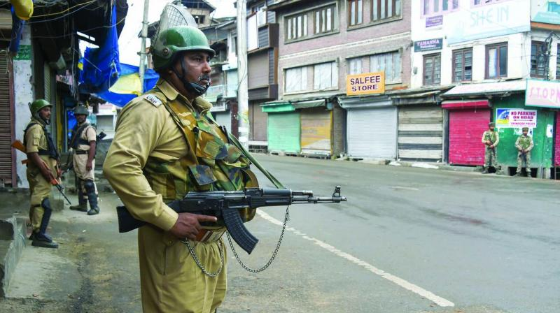 A security person stands guard during restrictions in Srinagar on Friday evening. (Photo: PTI)