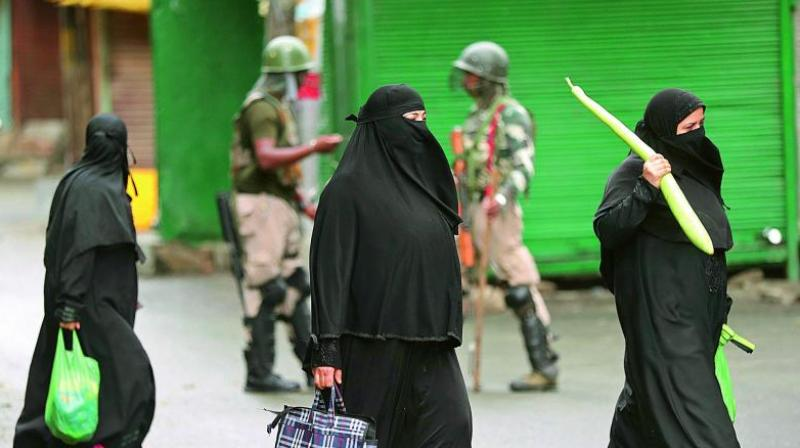 Kashmiri women holding bags of essential commodities walk past soldiers closing off a street in Srinagar on Saturday. (AP)