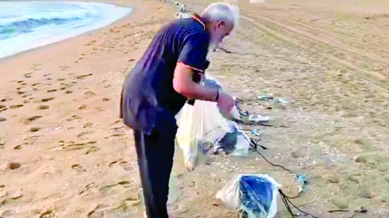 Prime Minister Modi takes a stroll on the beach and also picks litter near the resort in Kovalam on Saturday morning. (Photo: Asian Age)