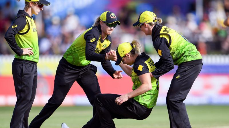Australia's Ellyse Perry is helped to her feet by teammates after being injured in their Twenty20 women's World Cup match against New Zealand in Melbourne on Monday. AFP photo
