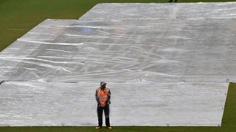 Covers are placed on the field as rain stopped play during the Twenty20 women's World Cup game between Pakistan and Thailand in Sydney on Tuesday. AFP Photo