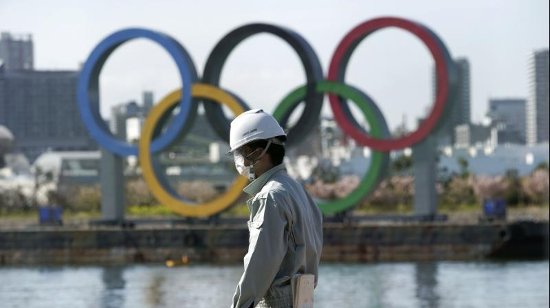 A masked man works at a construction site with the Olympic rings in the background on Tuesday. AP Photo