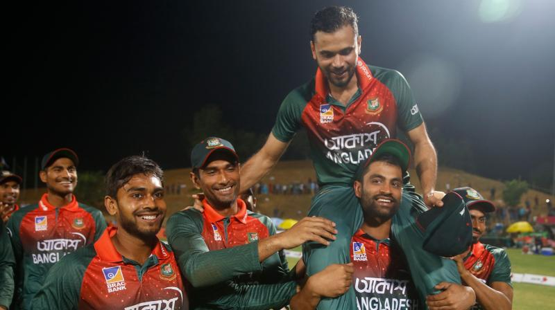 Bangladesh's captain Mashrafe Bin Mortaza is lifted by his teammate Tamim Iqbal after the third one day international against Zimbabwe in Sylhet on Friday. AFP Photo