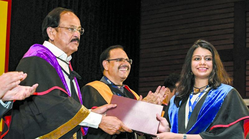 Vice-President Venkaiah Naidu felicitates a student. (Photo: PTI)