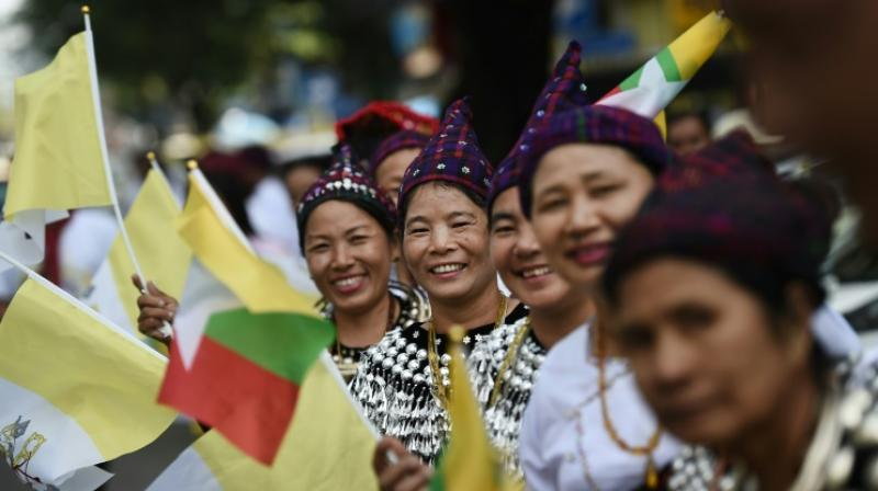 Catholics in colourful ethnic traditional dress waved flags and danced at Yangon's airport in a joyful welcome for the pope, making the first visit to the country by a pontiff. (Photo: AFP)