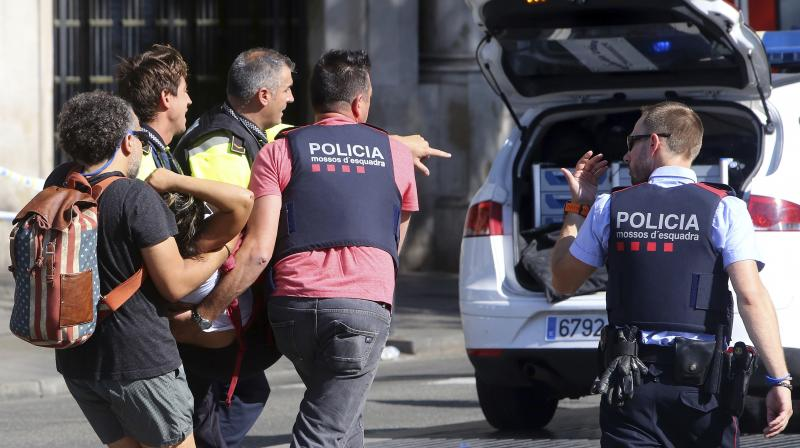 An injured person is carried in Barcelona, Spain, after a white van jumped the sidewalk in the historic Las Ramblas district, crashing into a summer crowd of residents and tourists and injuring several people. (Photo: AP/File)