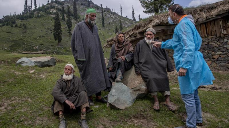 Kashmiri nomads listen to Dr. Sayeed Idrees during a COVID-19 vaccination drive in Tosamaidan, southwest of Srinagar. (Photo: AP)