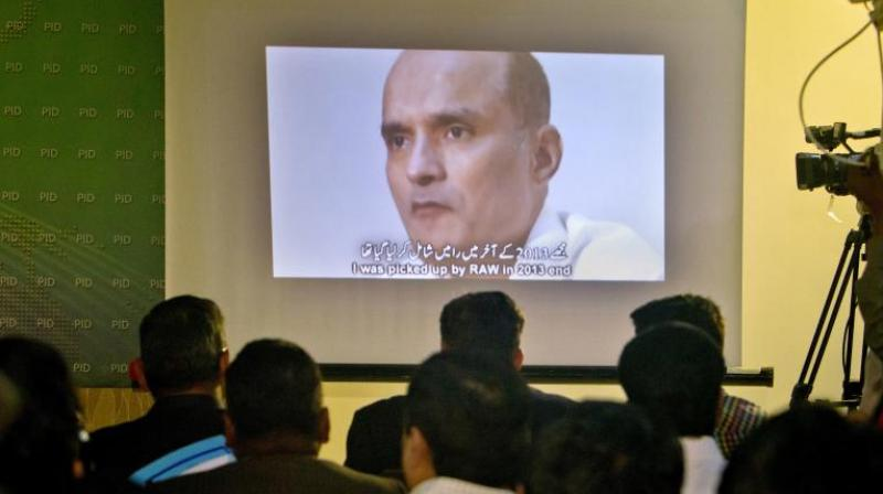 In this March 29, 2016 photo, journalists look an image of Indian naval officer Kulbhushan Jadhav. (Photo: AP)