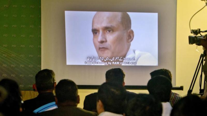 In this March 29, 2016 photo, journalists look a image of Indian naval officer Kulbhushan Jadhav. (Photo: AP)