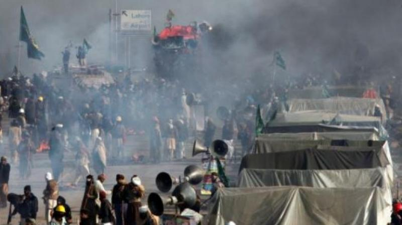 Demonstrators protest as police fire tear gas shells to disperse them during a clash in Islamabad, Pakistan. (Photo: AP)