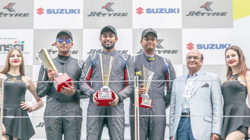 FMSCI National Championship Euro JK 17 winners Anindith Reddy (centre), Nayan Chaterjee (left) and Vishnu Prasad pose on the podium at the BIC in Greater Noida on Sunday. JK Tyre Industries CMD Raghupati Singhania gave away the awards.
