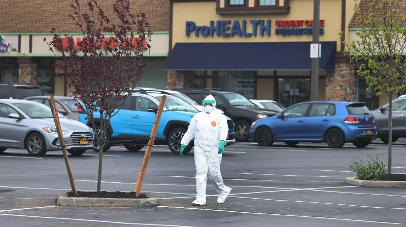 A Health Care Worker walks across the parking lot at the Pro Health Urgent Care coronavirus testing site in Wantagh, New York. (AFP)