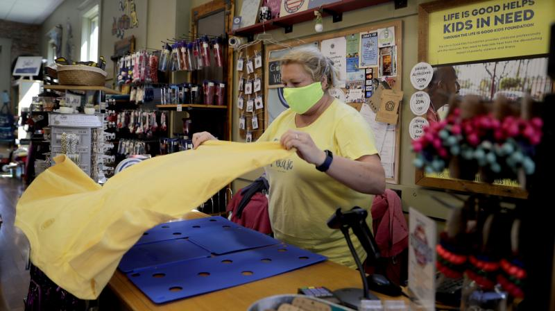 Amy Senter, owner of Jake's on Main, folds T-shirts in preparation for reopening her shop after being forced to close due to the coronavirus in St. Charles, Mo. (AP)