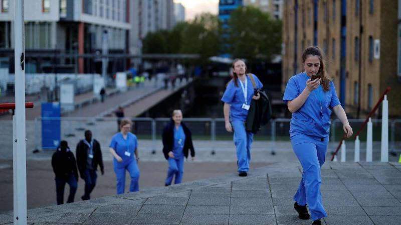 Medical staff from Britain's NHS (National Health Service) in scrubs walk outside the ExCeL London exhibition centre, which has been transformed into the