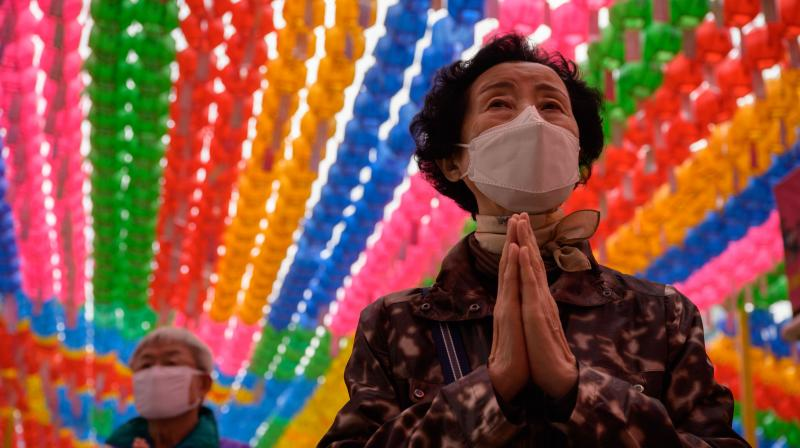 Worshippers wearing face masks attend a prayer ceremony entitled 'overcoming and healing the COVID-19 coronavirus', while marking Buhha's birthday at the Jogye buddhist temple in Seoul. (AFP)