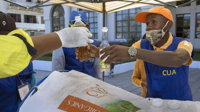 A man gets his bottle filled with a herbal extract believed to protect from COVID-19, in Antananarivo, Madagascar. (AP)