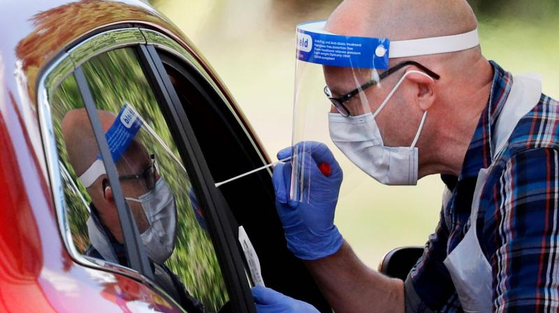 A medical worker takes a swab to test for the novel coronavirus COVID-19 from a visitor to a drive-in testing facility at the Chessington World of Adventures Resort, in Chessington. (AFP)