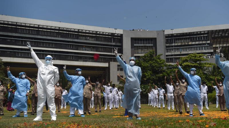 An Indian Navy helicopter (unseen) throws rose petals on the INHS Asvini (Indian Naval Hospital Ship) staff to pay tribute to all those involved in the fight against the spread of the COVID-19 coronavirus, in Mumbai. (AFP)