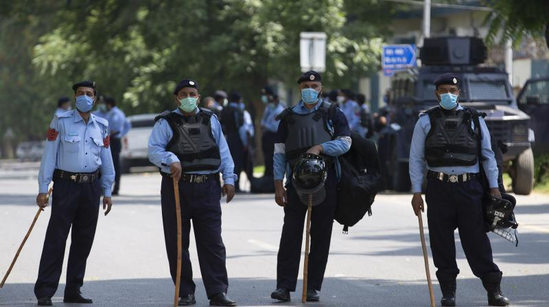 Police officers stand guard outside the Lal mosque which is sealed as its cleric denies a government-imposed nationwide lockdown to help contain the spread of the coronavirus in Islamabad. (AP)