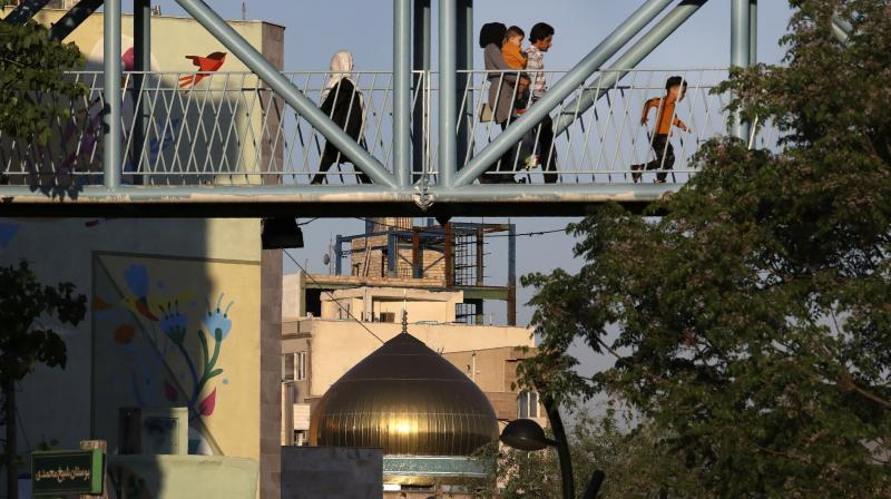 People walk on a pedestrian overpass near a mosque during the Muslim holy fasting month of Ramadan in southern Tehran. (AP)