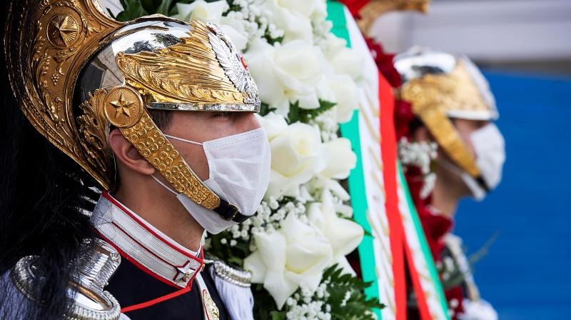Corazzieri Guards wearing protective face masks, as they place a wreath at the monument commemorating those killed at work, as people keep away from May Day (May 1) workers celebrations during the country's lockdown. (Photo taken in Rome and released by the Presidential Quirinale Palace press office)