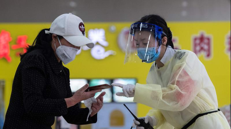 A staff member (R) wearing a face shield talks with a passenger at a long-distance bus station in Wuhan in China's central Hubei province. (AFP)