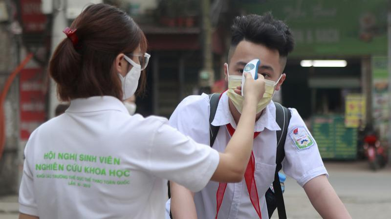 A student is scanned for temperature before entering Dinh Cong secondary school in Hanoi, Vietnam. (AP)