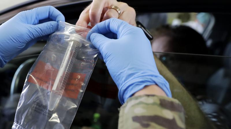 Passenger hands over his testing kit to Illinois National Guard soldier Carlye Clehouse at a testing facility in Waukegan. (AP)