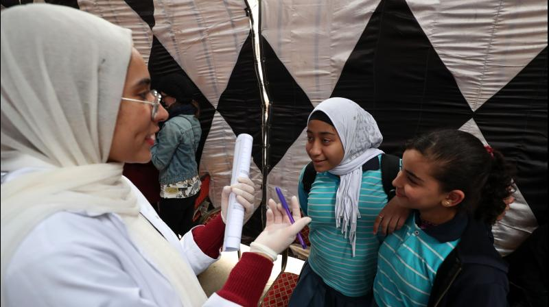 An Egyptian doctor gives medical advice to girls about Female Genital Mutilation (FGM) during an awareness campaign in Giza