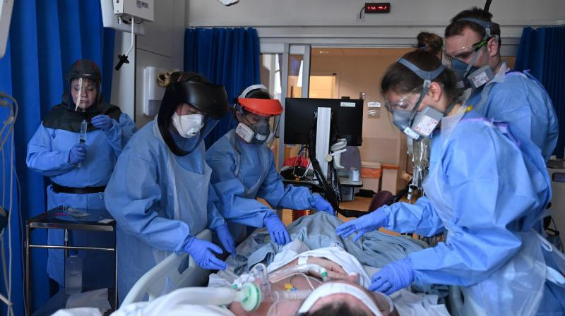 Clinical staff wear personal protective equipment (PPE) as they care for a patient at the Intensive Care unit at Royal Papworth Hospital in Cambridge. (AFP)