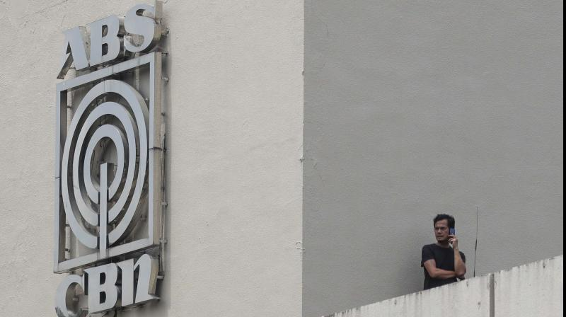 A man stands next to a logo at the headquarters of broadcast network ABS-CBN Corp. (AP)