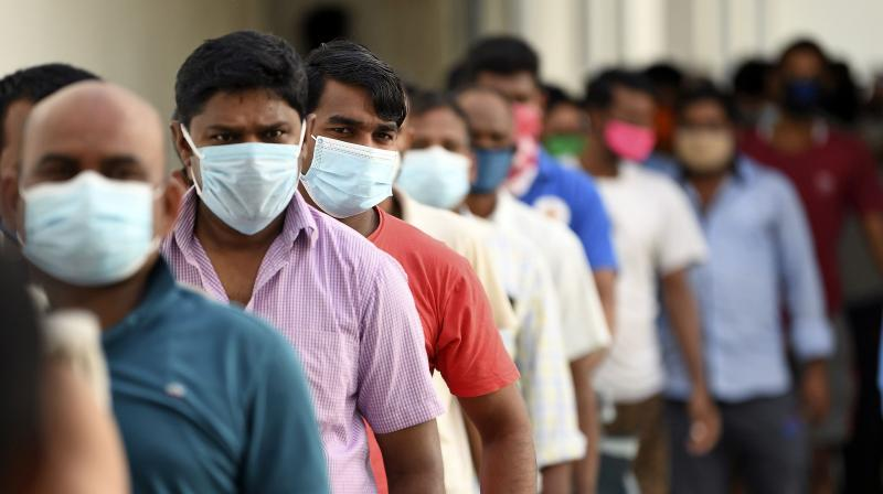 Foreign workers wearing protective masks keep distance from each other as they queue in Dubai. (AFP)
