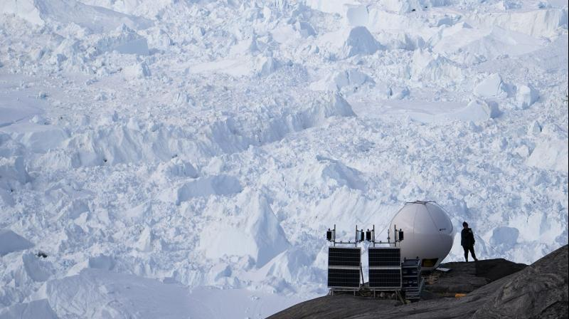 A woman stands next to an antenna at an NYU base camp at the Helheim glacier in Greenland. (AP)