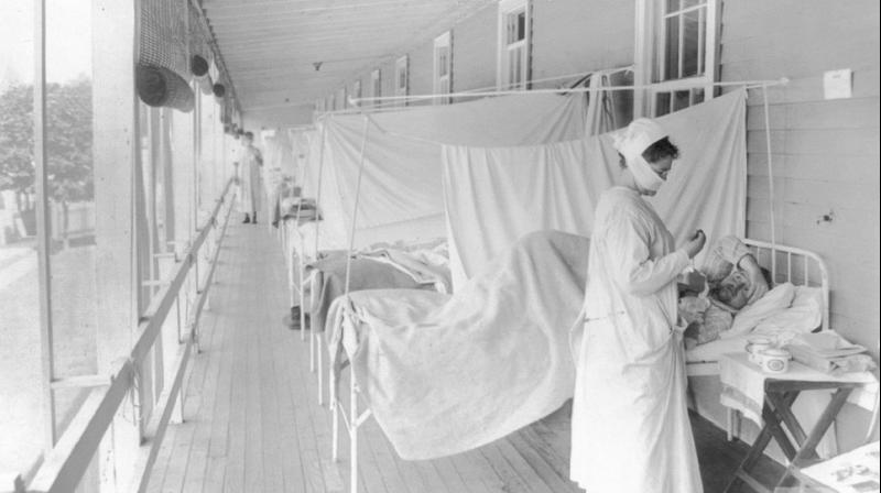 A nurse takes the pulse of a patient in the influenza ward of the Walter Reed hospital in Washington. (AP)