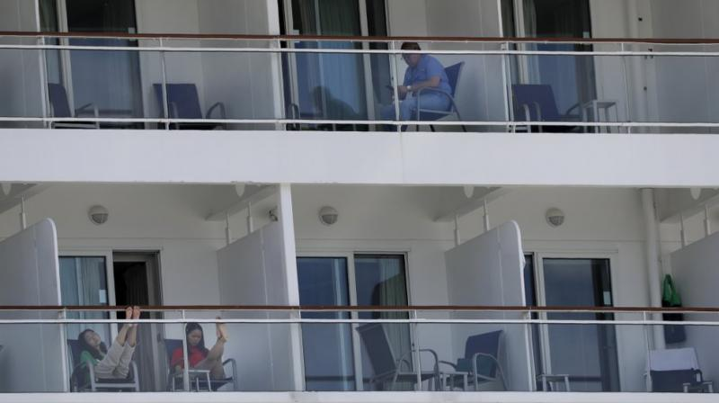 People aboard the Norwegian Epic cruise ship docked at PortMiami in Miami, sit on their balconies. (AP)