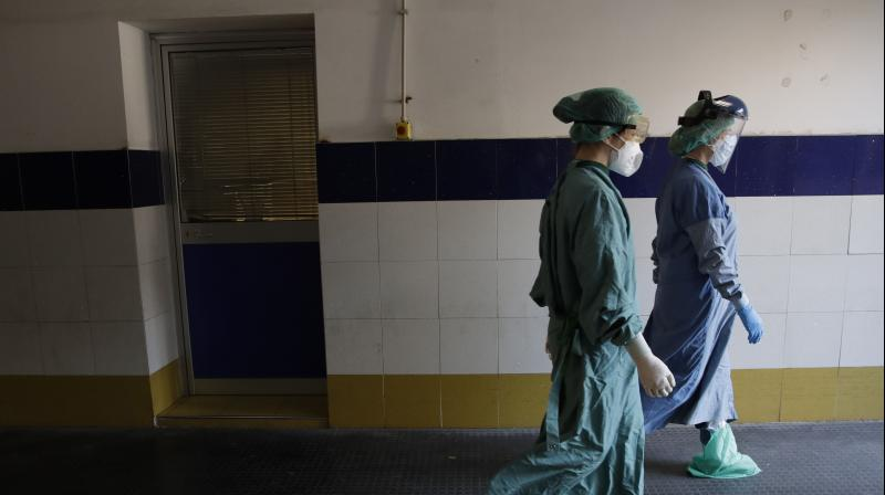 Medical staffers walk in hall leading to the COVID-19 emergency ward of the Santo Spirito hospital, in Rome. (AP)