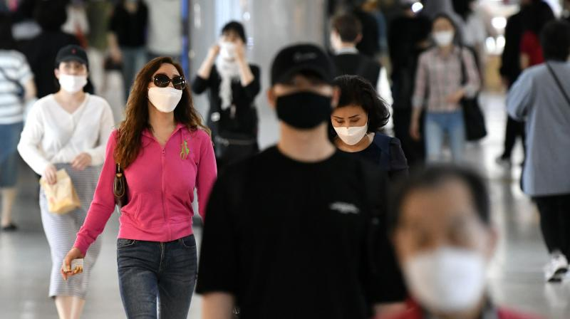People wearing face masks walk through an underground shopping area in Seoul. (AFP)